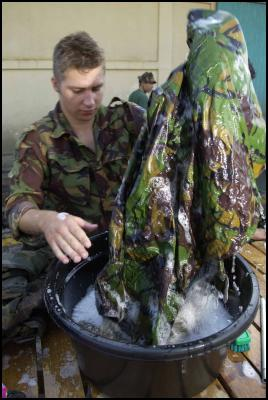 Timor, New Zealand Defence Force: Private Chris Sinclair cleans his equipment to tough MAF standards
