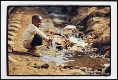 A child collecting drinking water from a water source in a slum in Kenya. Source: Phill Prendeville