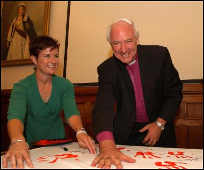 From right:  the Assistant Anglican Bishop of Auckland, Richard Randerson, pledges his support with a hand print, while Every Child Counts Project Manager Deborah Morris-Travers, looks on.