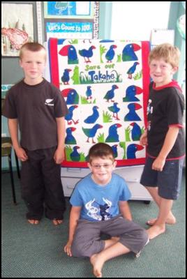 Students Jordan Robinson, Matt Peel and Connor Close pose with their takahe quilt