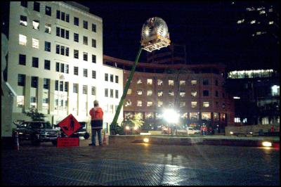 Fern sculpture ('Fernball') being held by a crane as it is taken down for repairs in Civic Square, Wellington