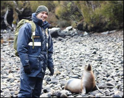 Sub Lieutenant Piers Routledge with a New Zealand Sealion, Tagua Cove, Auckland Islands.
