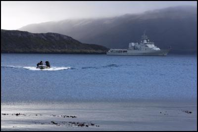 Navy inflatable operating in Tagua Cove in the Auckland Islands. HMNZS WELLINGTON in background.