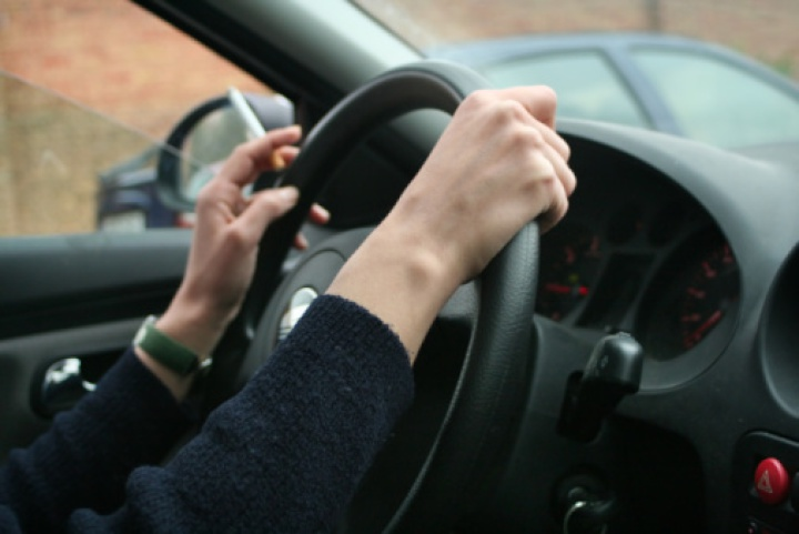 woman's hands on steering wheel, holding cigarette