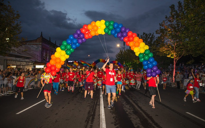 parade with rainbow arch made of balloons