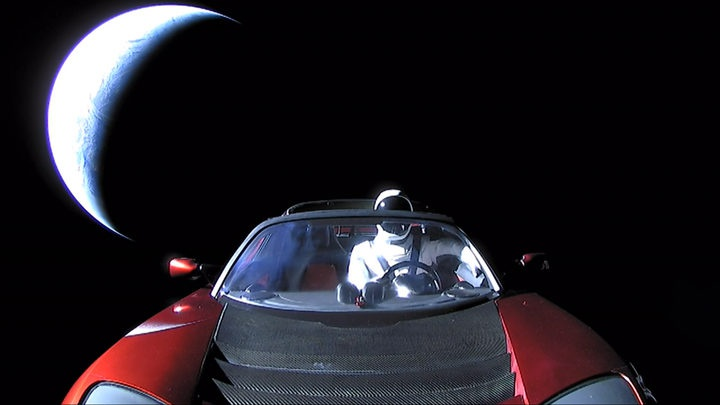 an open convertible car in space, with a space suit in the driver's seat