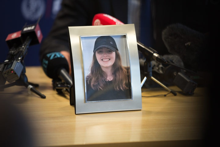 a frame photo of Grace Millane with press conference microphones