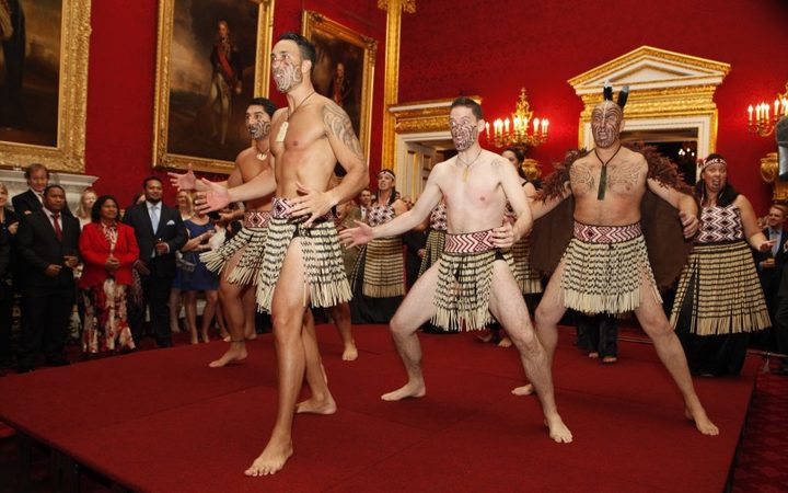 traditionally-dressed haka performers on a platform stage in a sumptuous room