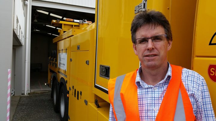 Mark Owen wearing an orange safety vest, standing in front of a big yellow vehicle