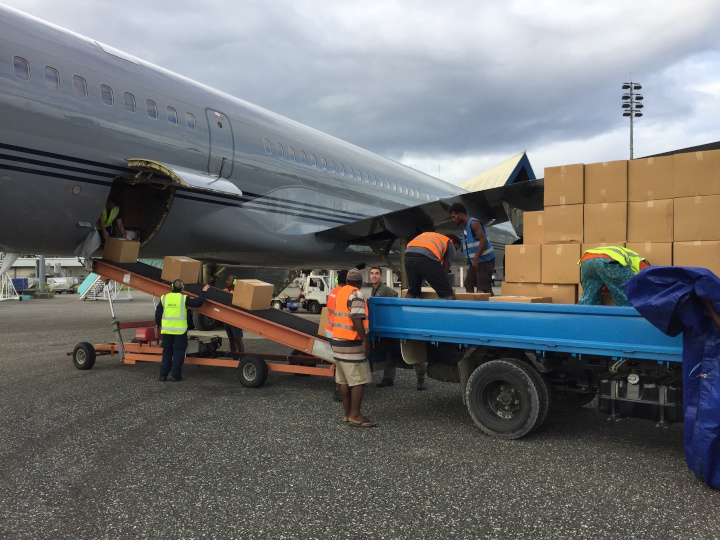 people loading cardboard boxes from an airplane to a flatbed truck