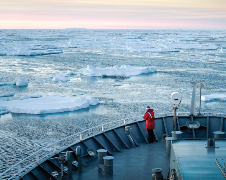 a person on the deck of a boat with floating chunks of sea ice around it