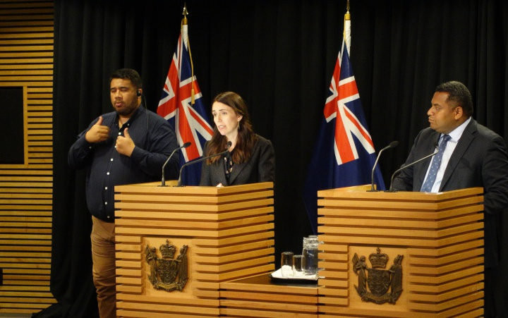 jacinda ardern with sign translator and kris faafoi