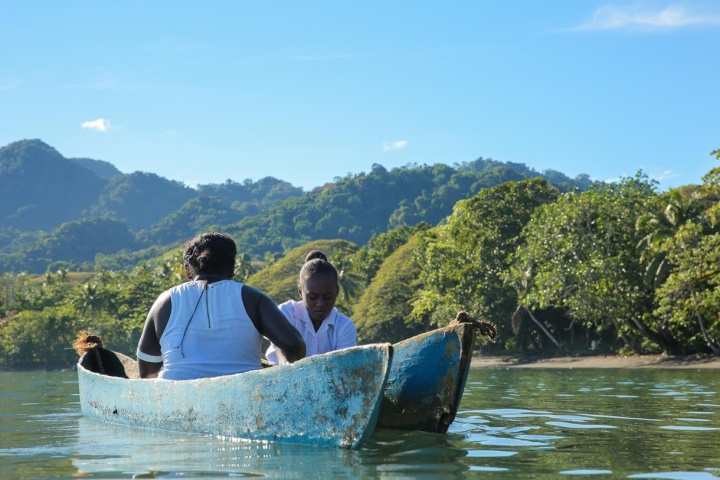 two women in a small double-hulled boat off forested land