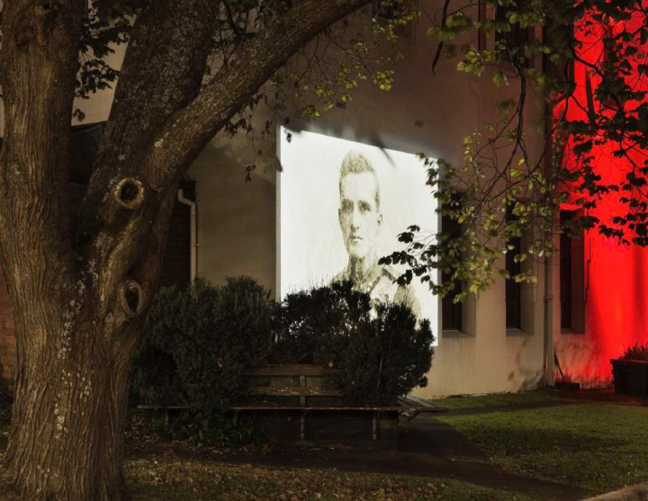 an old head and shoulders photograph of a soldier, projected onto the side of a building, seen through trees and bushes of a small plaza