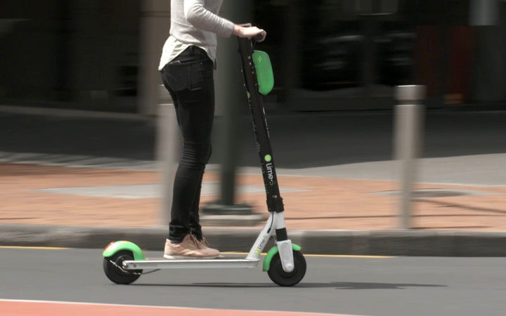 a person riding a lime scooter on a road, with background blur suggesting speed