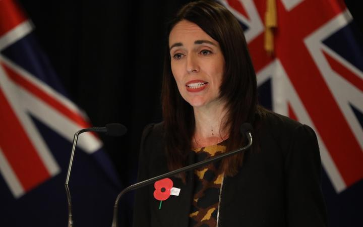 Jacinda Ardern at the press conference, wearing an Anzac oppy with flags in the background