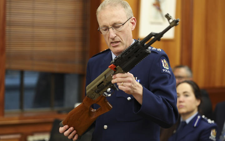 a police officer showing features of a gun in a select committee room