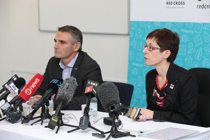 two people sitting at a table with press conference microphones