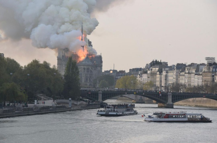 fire burning in nortre dame cathedral, seem from the seine river with boats and a bridge in the foreground. Flames are in the roof but the spire is standing in this picture