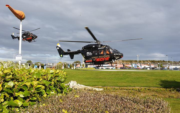 two helicopters, low over a grassed landing field