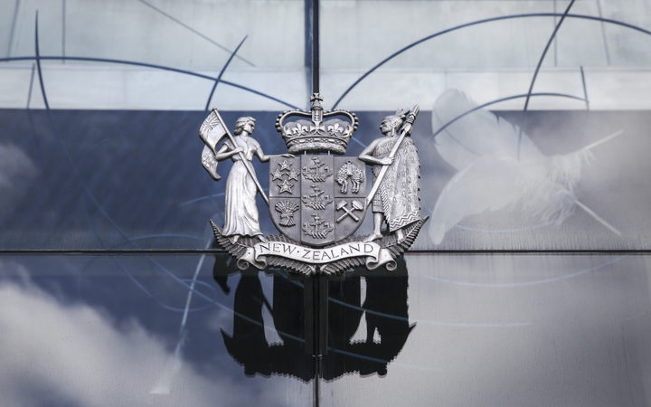 the nz coat of arms in brass on the glass wall of a court building