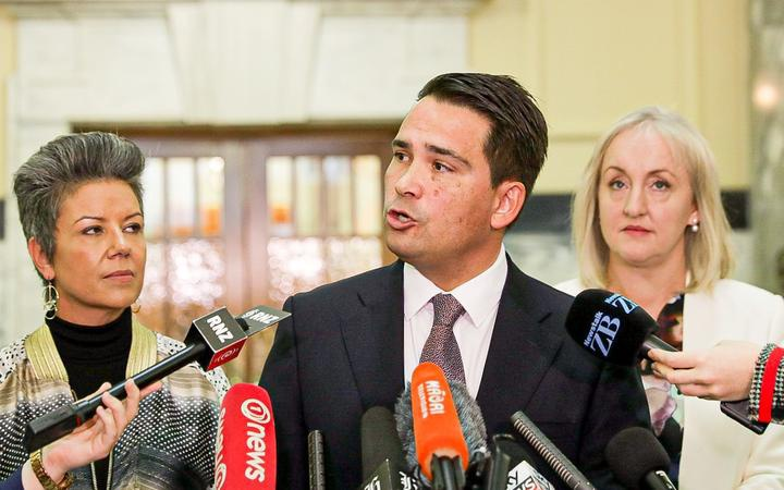 Simon Bridges speaks into media microphones at Parliament, flanked by Paula Bennett and Amy Adams