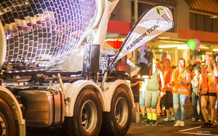 people in orange vest parading behind a concrete truck with the mixer decorated as a mirror ball