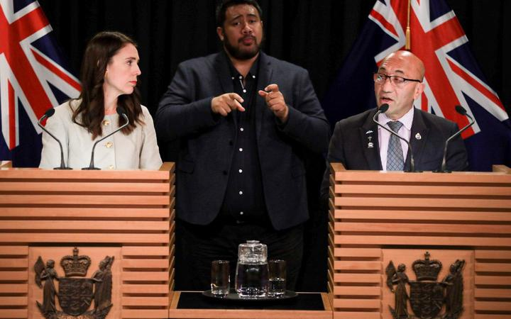 ardern and mark at the beehive press conference, with sign language translator