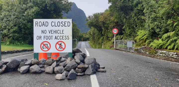 piled stones and a warning side across one side of the road