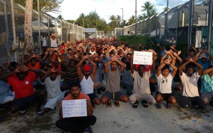 a large group of men with security fence on both sides, squatting with their arms crossed over their heads or holding placards