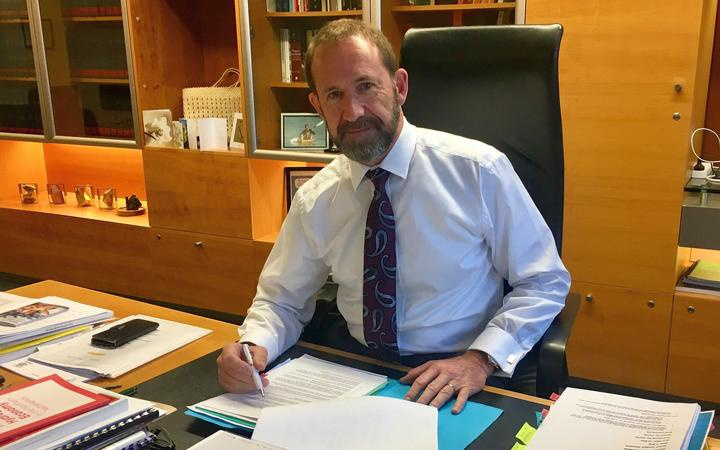 andrew little at his desk, posing with a pen and papers