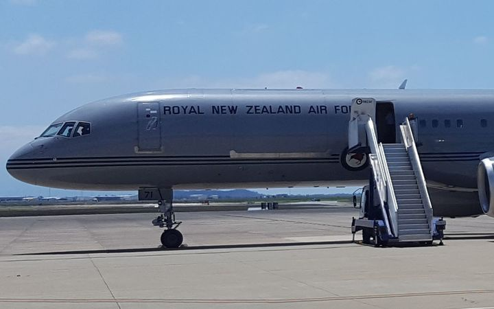 a 757 with 'royal new Zealand air force' written on the side, at an airport with the door open and stairs attached