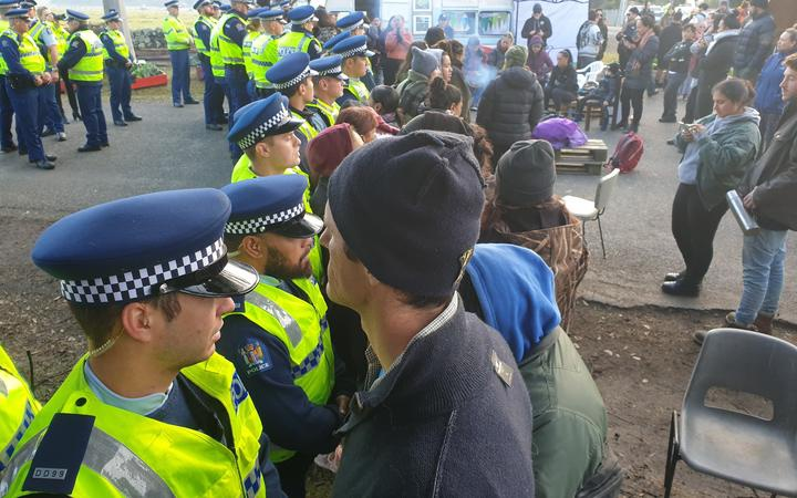 people facing off with a line of police. More police and protestors stand around behinds the lines. In the background some protestors are on seats around a small fire