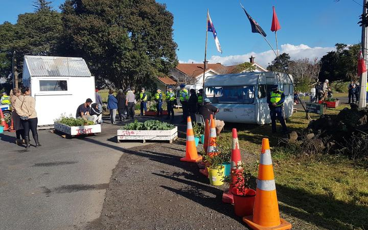 some large planters and a small shed across an entrance road, with a mobile camper behind them. Police for a line across the road and other people stand in small clusters