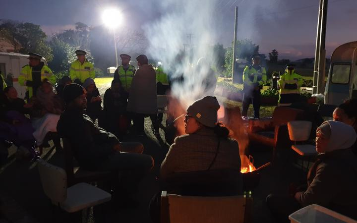 at night,protestors sitting on seats arranged around a containedfire, in front of a line of police