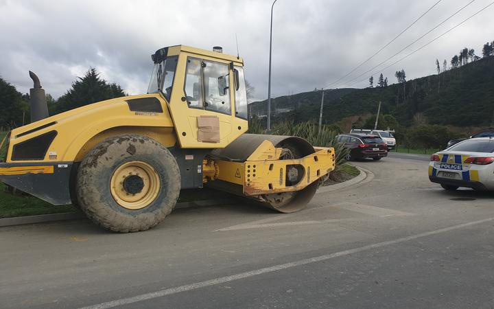 A road roller stopped at the side of a road, with a police car nearby