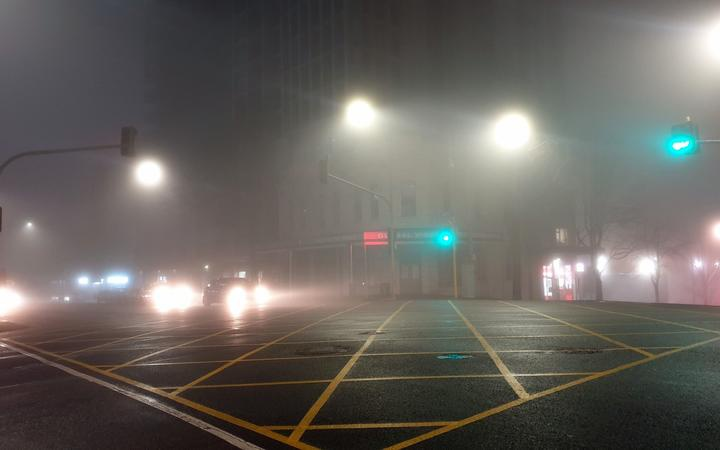 a photo of a city intersection at night with street and car lights showing through fog