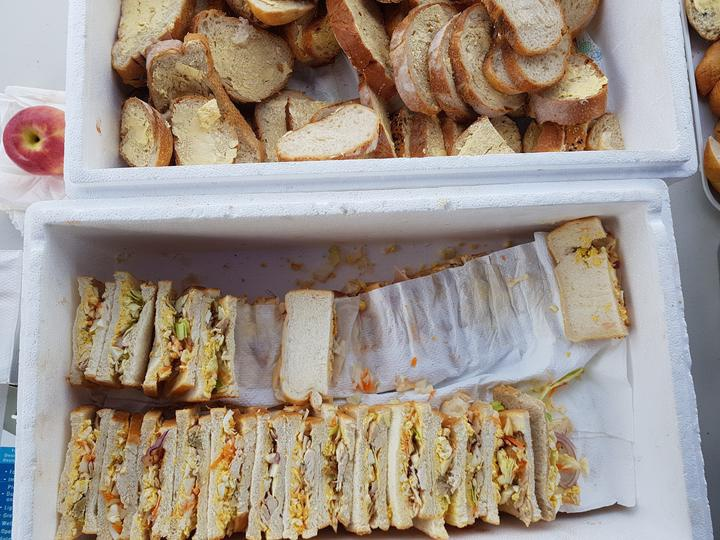 a lot of sandwhiches in a box, beside another with buttered slices of bread stick