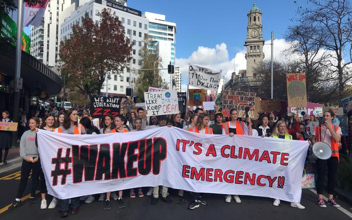 a crowd of young protestors in the street led by a banner saying '#wakeup it's a climate emergency'