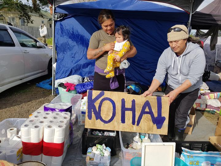 a woman holds a 'koha' sign over boxes of toiletries and other items