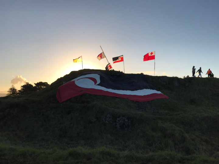 a very large tino rangatiratanga flag draped on a hill, with other flags on poles at the top and the sunset behind
