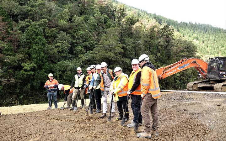 ten people in high visibility gear and hard hats, holding spades against ground that has already been worked on, possibly the digger in the background