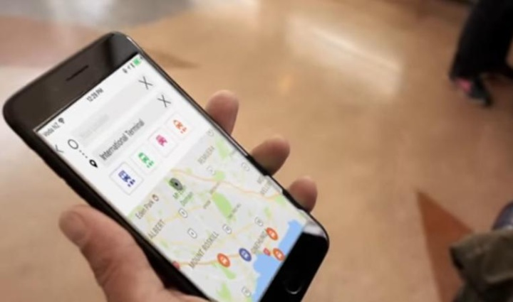 someone holding a phone with a journey planning app showing travel mode options and a map with a search for 'international terminal'