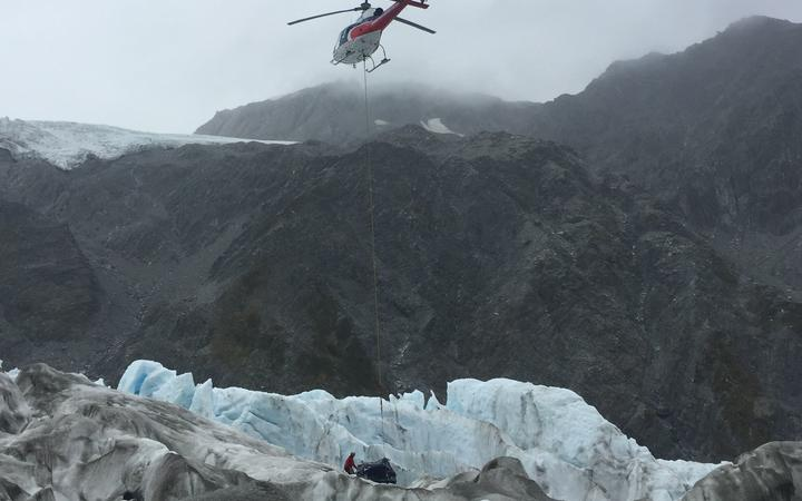 a helicopter hovers with a line attached to a large package on the glacier, with a person touching the bundle's side
