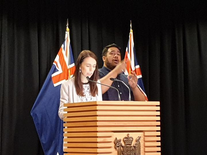 Jacinda Ardern at a Beehive press conference with a sign interpreter