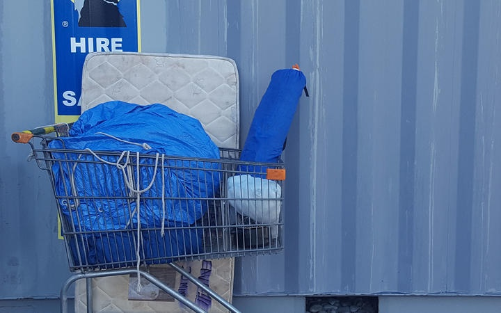 bundles of stuff in a shopping trolley and a matress