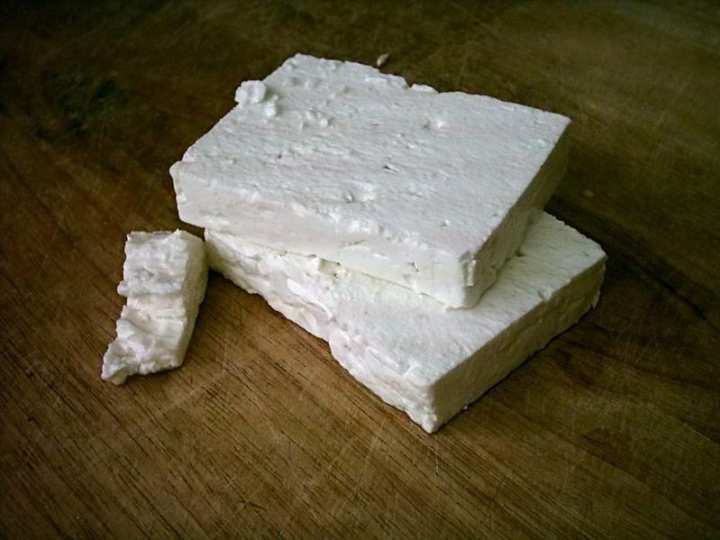 wide blocks of feta cheese on a wooden surface