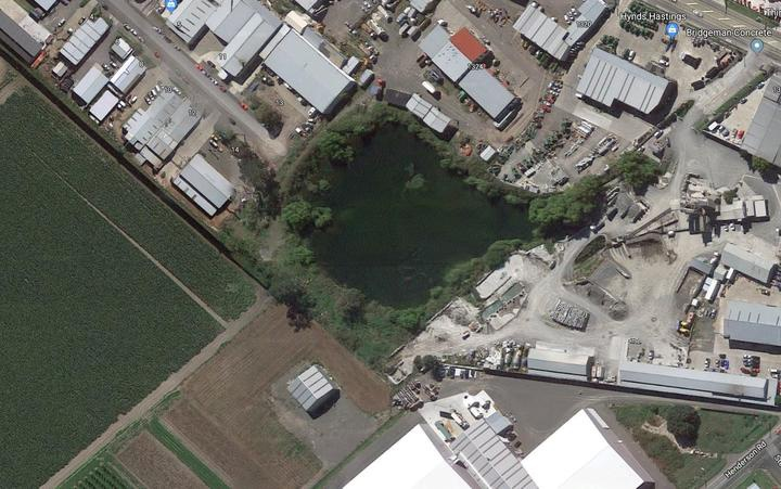 view from above of a lake surrounded by plants in the between industrial and farm land