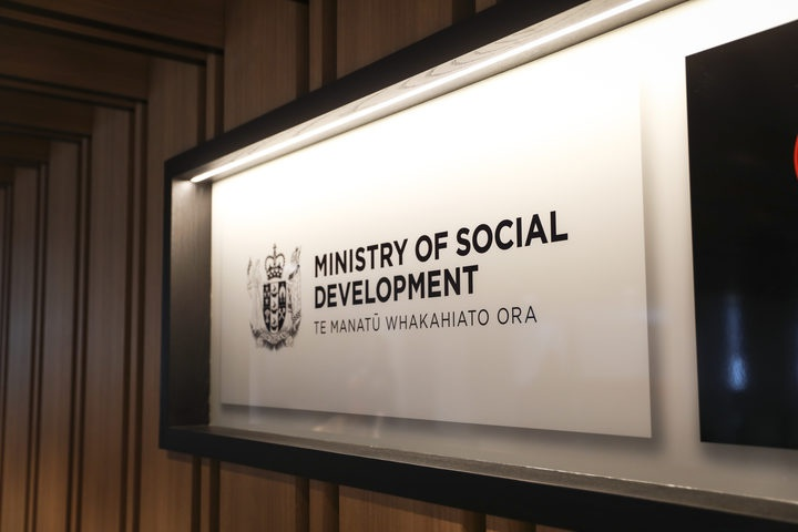 a sign for the Ministry of Social Development in a wall case in a building