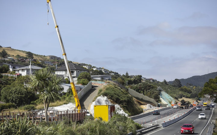 a crane working beside the operating motorway